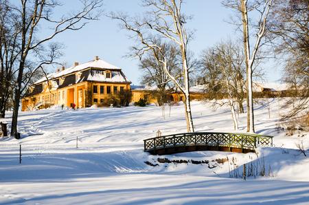 Wooden arch footbridge on a snow covered landscape. Bogstadvannet area in Oslo, Norway. Winterscape
