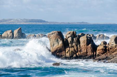 Big waves crashing on rocks coastline. Sunny day