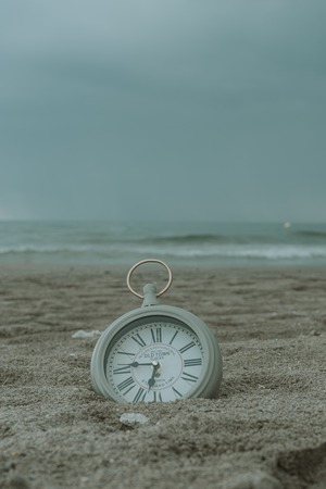 Clock on the beach sand in vertical