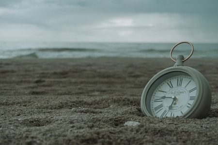 Clock on the beach sand giving a feeling of bed and relaxation