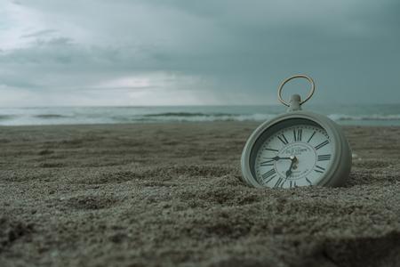 Reloj en la arena de la playa dando una sensación de cama y relajación.