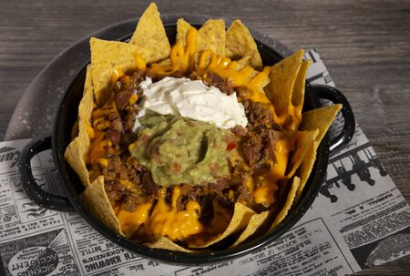 Plate of nachos with chili, sour cream guacamole and cheddar sauce on wooden table. Isolated image