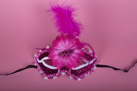 Elegant Venetian mask of fuchsia color on pink background. Take from above. Festive concept