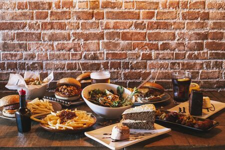 Variety of restaurant menu dishes. Salad with goat cheese, homemade hamburgers and fries, drink, chicken wings, vegetable tempura and cake on the wooden table.