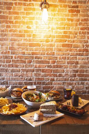 Variety of restaurant menu dishes. Salad with goat cheese, homemade hamburgers and fries, drink, chicken wings, vegetable tempura and cake on the wooden table. Vertical Image
