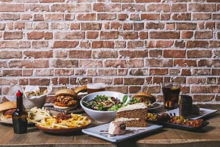 View of the table with a variety of dishes, hamburgers, fries and salad, drinks, chicken wings, sauce, cake and desserts on the wooden table. Restaurant menu. Stock Photo