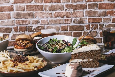 View of the table with hamburgers, french fries and salad, drinks and cake on the wooden table, isolated image.