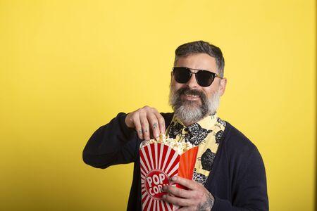 ポップコーンを笑って食べる黄色の背景に白いひげとサングラスを持つ男。映画のコンセプトにおける人々の感情。映画を見て、ポップコーンのバケツを持っています。 写真素材