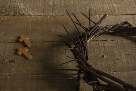 Close-up of two small wooden crosses and a representation of the crown of thorns of Jesus Christ on a wooden surface