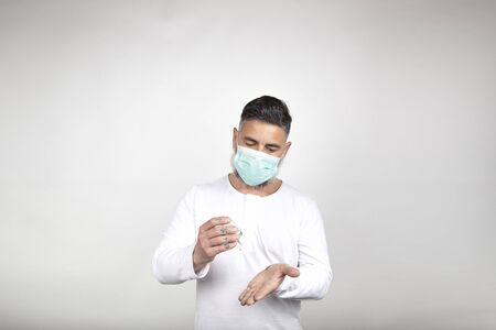 Man with surgical mask uses a disinfectant to clean his hands of germs on white background. Coronavirus prevention concept. Epidemic