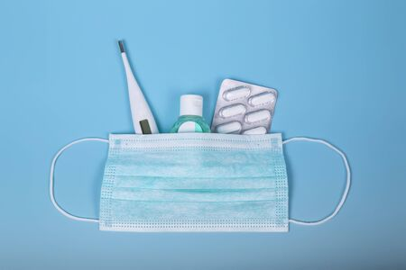 Protection products for treatment. Surgical mask, thermometer, disinfectant gel and medications to prevent illness on a blue background. Coronavirus or covid-19 concept.