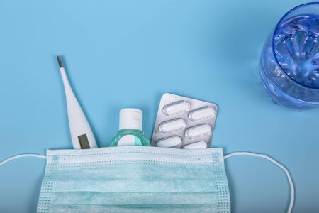 Protection products for treatment. Surgical mask, thermometer, disinfectant gel, medications and a glass of water to prevent disease on a blue background. Coronavirus or covid-19 concept.