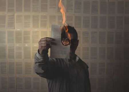man holding a burning book sheet and looking through it. Conceptual image.