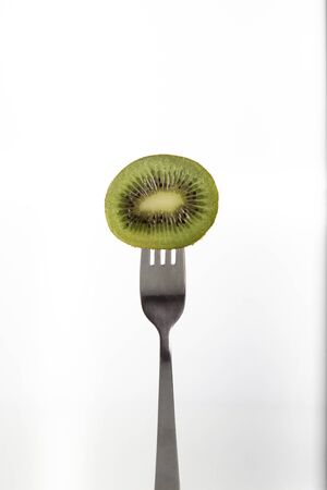 A half of a kiwi pierced on a fork over white background