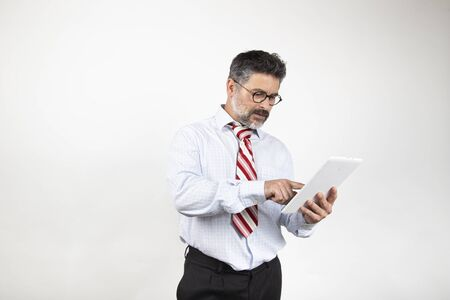 Surprised man in suit reading and typing on his tablet on white studio background