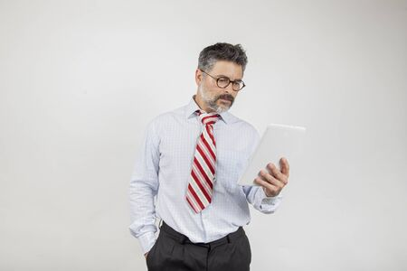 Portrait of businessman with glasses is reading the news on a digital tablet, isolated on white background.
