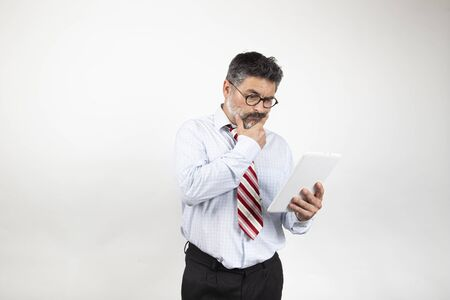 Portrait of classy serious Caucasian businessman in suit and glasses using tablet to read news on white background. Zdjęcie Seryjne
