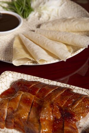 Isolated image of Peking lacquered duck accompanied by crepes and sauce. Vertical image