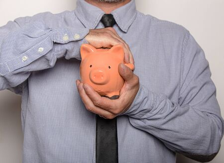 Businessman holding a piggy bank in hands isolated on white background