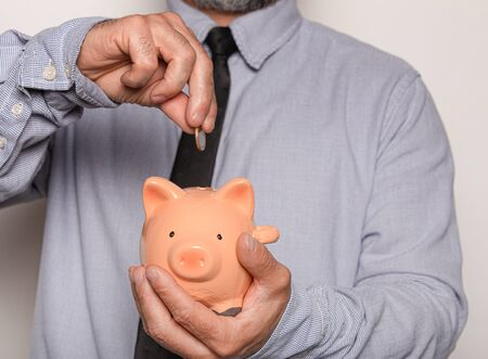 Businessman putting coins into small piggy bank on white background