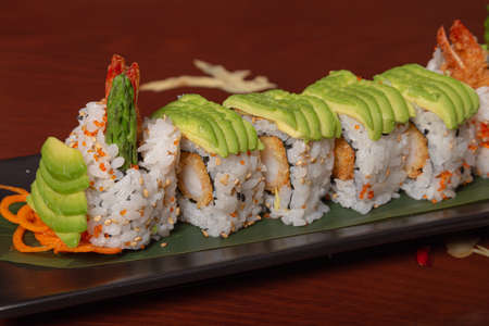 Grilled salmon sushi wrapped with avocado, prawn tempura and cheese on wooden table. Isolated image