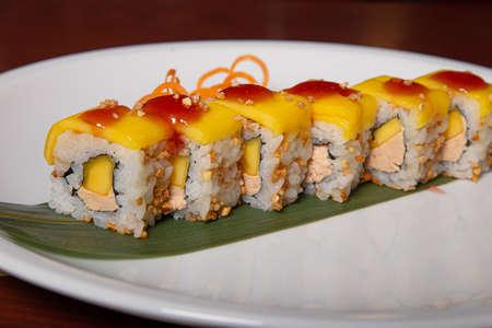 Mango sushi, foie gras, peanut and mango sauce served on a white plate. Japanese cuisine