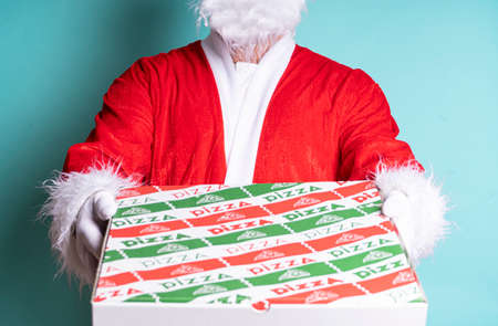 Closed portrait of Santa Claus holding a pizza box on blue background