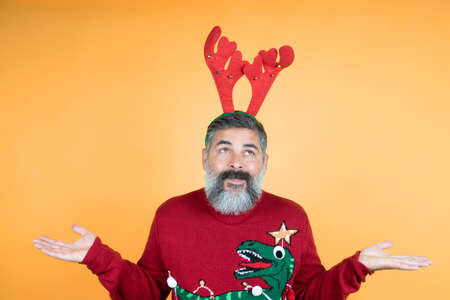 I will be Rudolf in 2021 Photo of a charming man with a white beard, a man shrugging, shoulders in a good mood demonstrating his new year, traditional red horns on his head, isolated background
