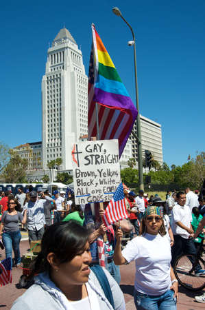 Los Angeles, USA, May 5, 2010: Immigration march with a gay flag and the City Hall in the back
