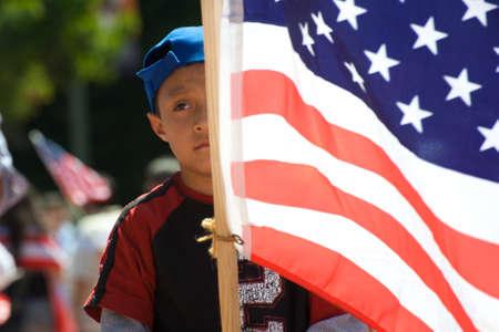 racismo: Los Angeles, EE.UU., 5 de mayo de 2010: Muchacho sosteniendo una bandera estadounidense durante una marcha de inmigración en el centro de Los Ángeles Editorial