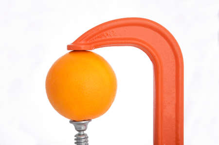 squeeze: Clamp squeezing an orange Stock Photo
