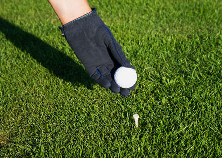 Golfer with the glove hand to put the ball on the tee peg photo