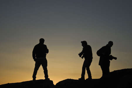 Silhouettes of photographers at sunset photo