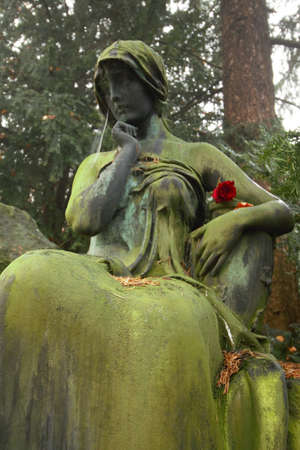 A woman statue sitting on a tombstone with a red rose Reklamní fotografie