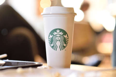 PENANG, MALAYSIA - 09 JUNE 2019: Starbucks take away coffee cup with logo, bokeh interior background. Starbucks is the world's largest coffee house with over 20,000 stores in 61 countries.