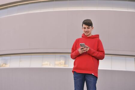 young man with red clothes at the door of his work writing a text message with his smarthphone