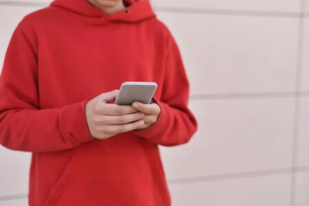happy young man in red clothes talking on his smarthphone, managing telecommuting work from home due to COVID-19
