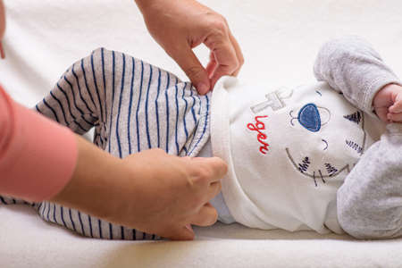 Mom changing a diaper on newborn baby