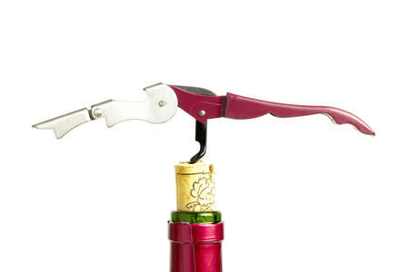 uncork: A corkscrew extracts the cork from a bottle of red wine  The bottle is green and red capsule  Stock Photo