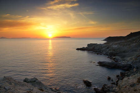 pone: Hermosa puesta de sol cerca de la playa de Ampeli, Folegandros  Al fondo el sol se pone sobre la isla de Milos  Stock Photo