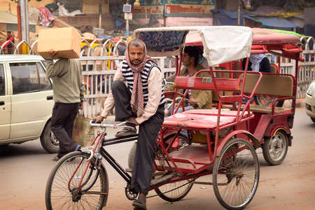 DELHI, INDIA - FEB 8, 2014  A rickshaw driver is looking for costumers in a street of Delhi  Editorial