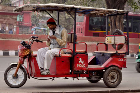 auto rickshaw: DELHI, INDIA - FEB 8, 2014  A autorickshaw driver is waiting costumers in a street of Delhi  Editorial