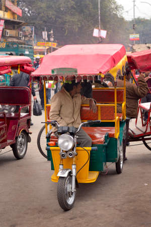 costumers: DELHI, INDIA - FEB 8, 2014  A autorickshaw driver is looking for costumers in a street of Old Delhi