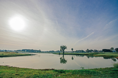 off course: Beautiful view of green golf field next to a water hazard in late morning sunlight. Hobby, leisure and activity concept.