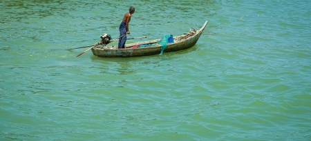 Old fisherman going out to sea in the Gulf of Thailand photo