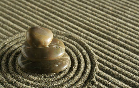 Three zen stones balancing in a sand garden.