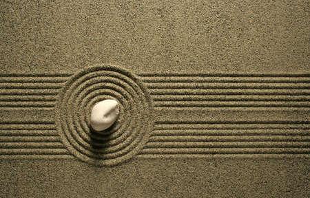 Ein einzelner Stein sitzen in einem Sand-Garten.
