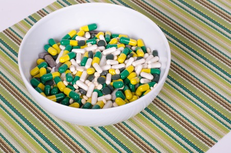 malady: Plate of pills on striped cloth isolated, concept diet, diseases
