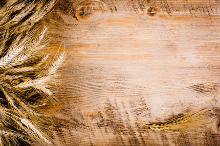 ears of wheat on wooden background. Card