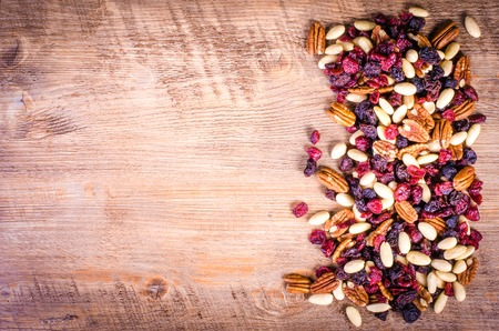 Dried fruits - pecan, cranberry, raisin, almond on wooden background. Reklamní fotografie - 46696816